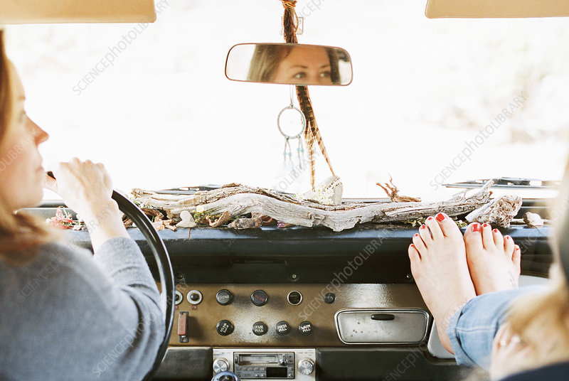 A woman in a jeep, feet on dashboard