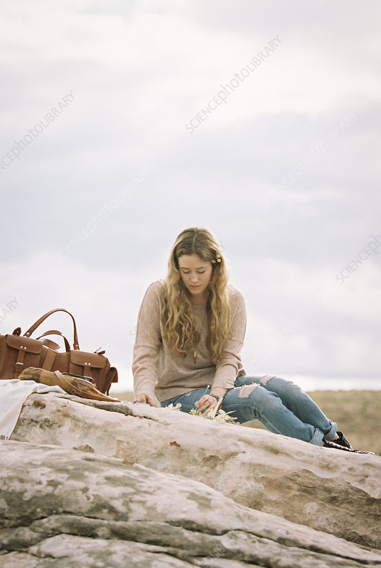Woman on a rock with a journal and pen