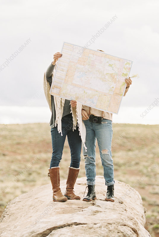Two women holding map hiding their faces