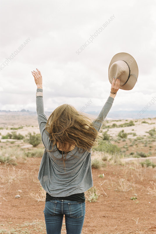 Woman standing in the desert, arms raised