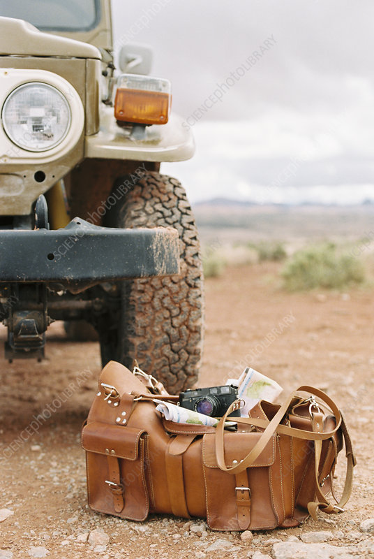 Leather bag, camera and map by jeep