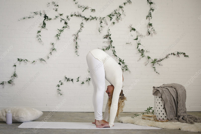 Woman in yoga pose bending forwards
