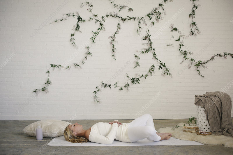 Woman lying on a white mat in a room