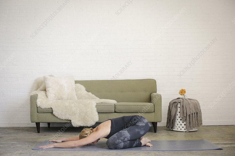 Woman kneeling stretching on a yoga mat
