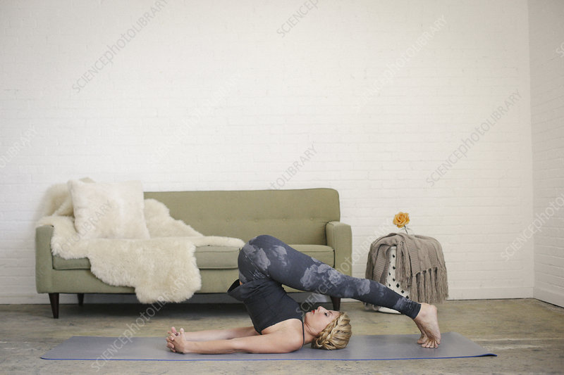 Woman lying on a yoga mat in a room
