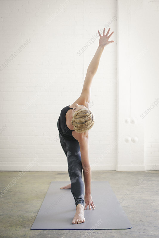 Woman on a yoga mat arms raised