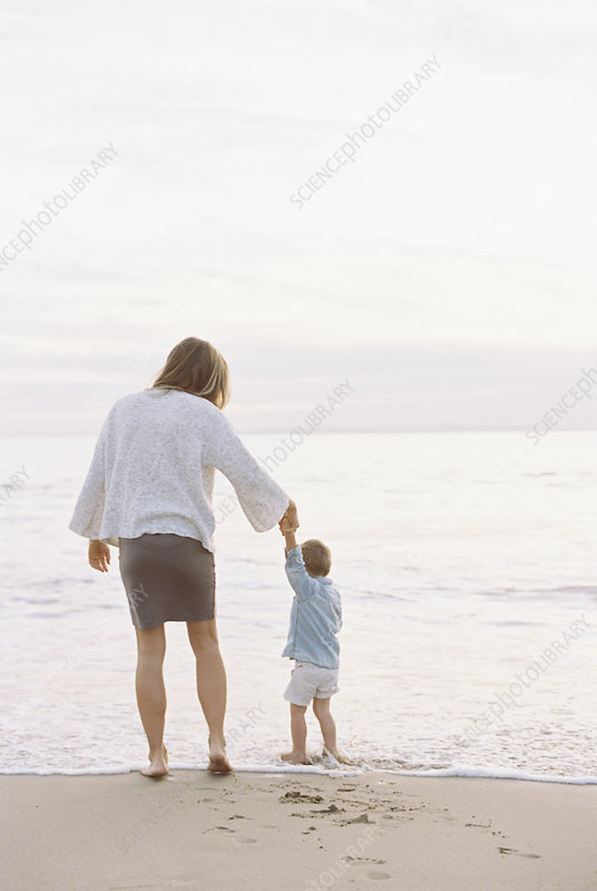 Woman on a beach holding a child's hand