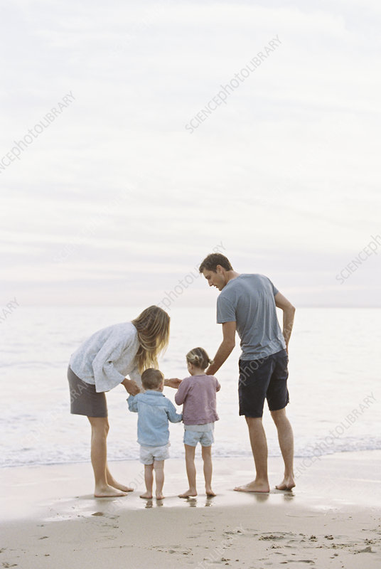 Couple playing with two children on beach