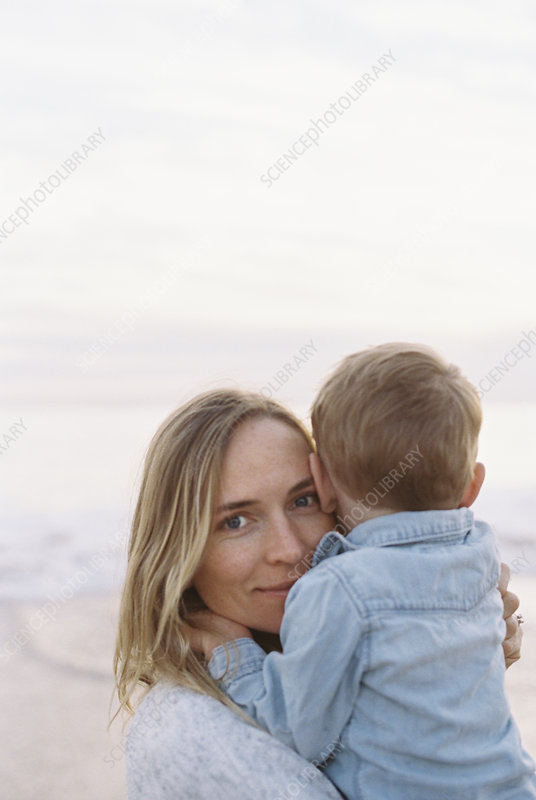 Woman on a beach holding a young boy
