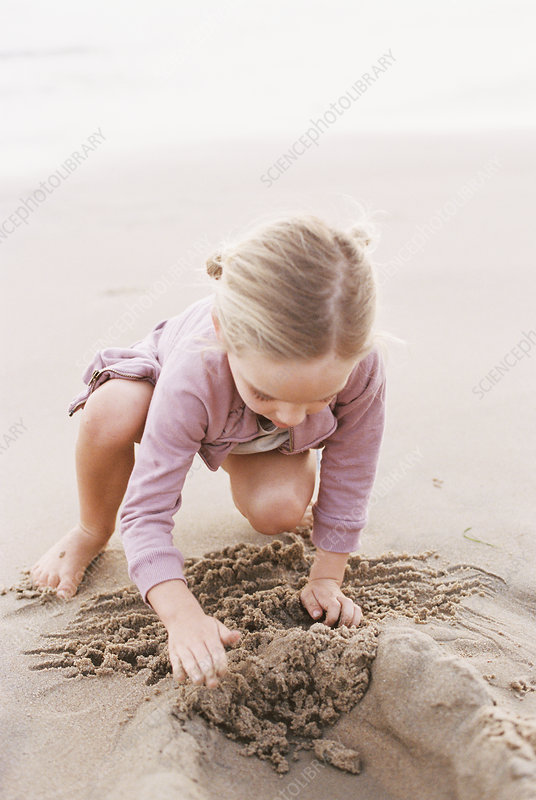 Young girl playing in the sand