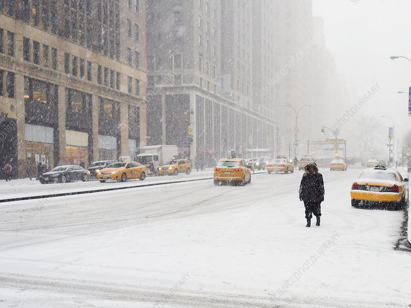 Man walking in a city in a blizzard