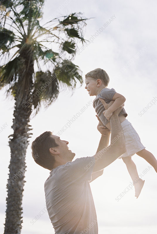 Man lifting his son into the air