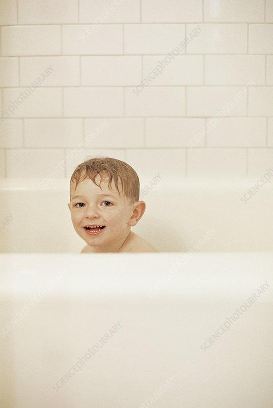 Young boy having a bath in tub