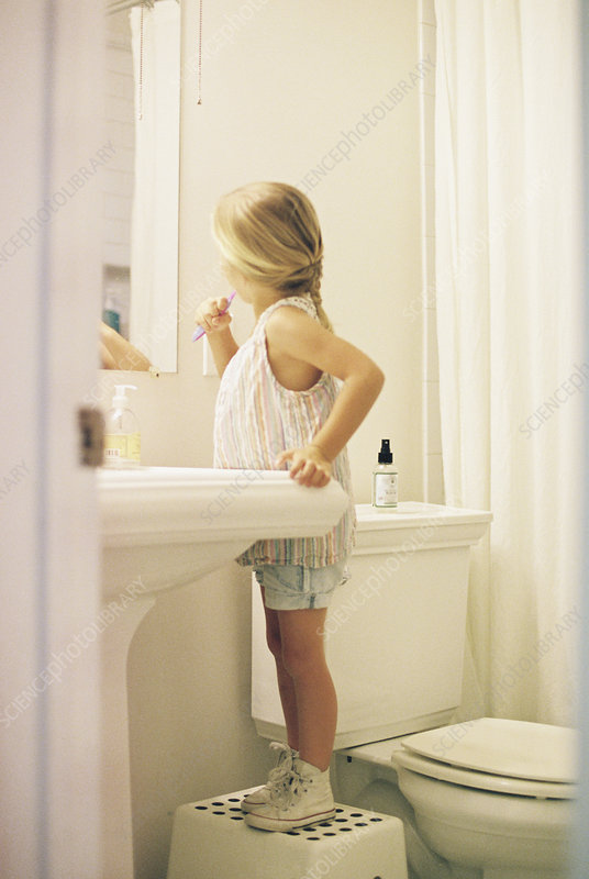 Young girl on a stool brushing her teeth