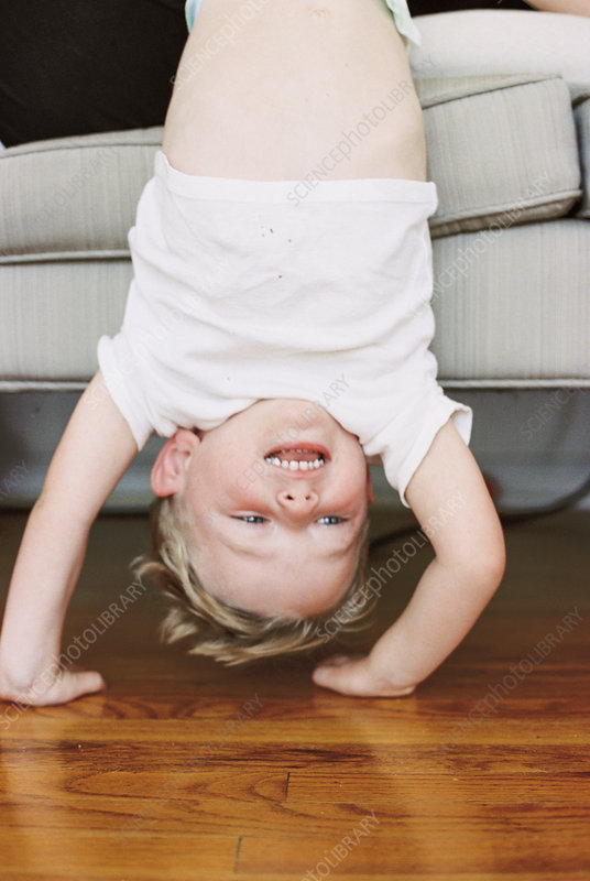 Young boy doing a handstand on a sofa