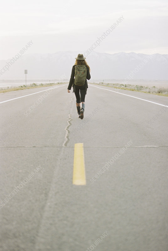 Woman walking down an empty road