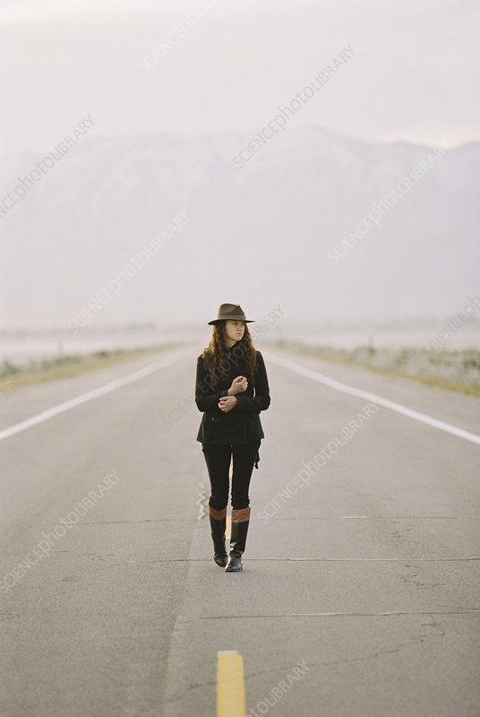 Woman walking down deserted country road