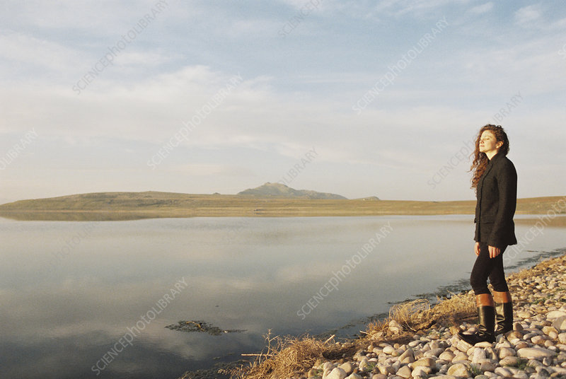 Woman standing on the shore of a lake