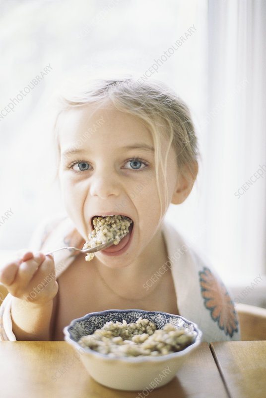 Young girl eating breakfast from a bowl