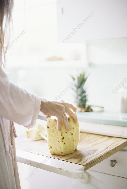 Woman cutting a fresh pineapple