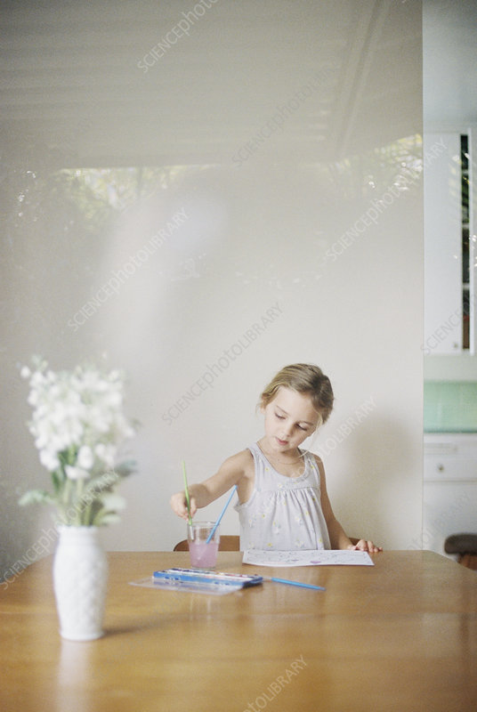 Young girl painting picture of flowers