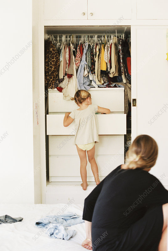 Young girl searching in drawers