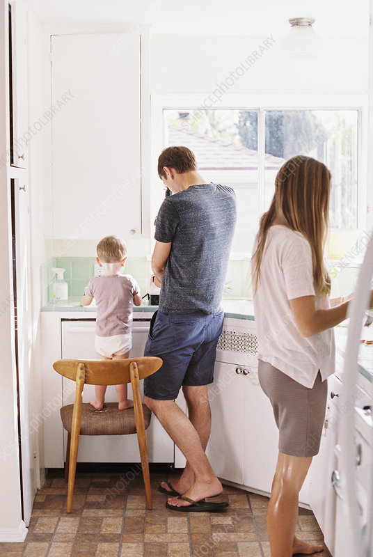 Couple standing in a kitchen with a child