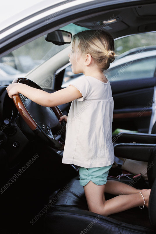 Girl kneeling on drivers seat of a car