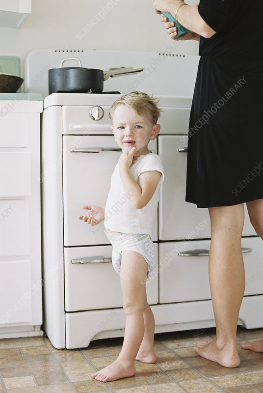 Woman and boy standing barefoot at home