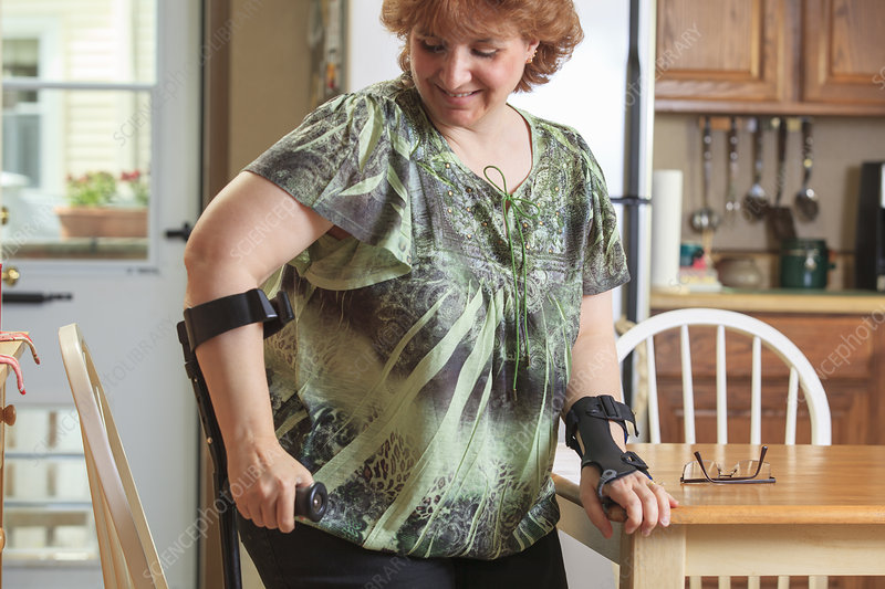 Woman using her hand brace and crutch