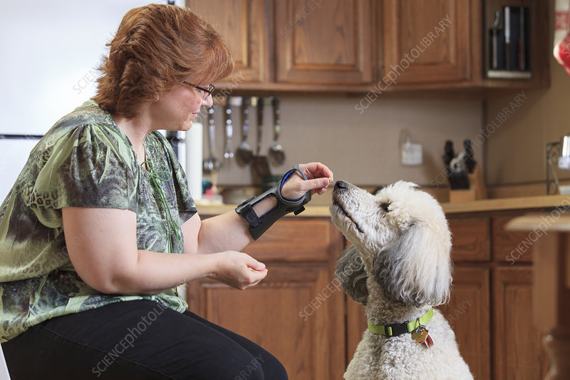 Woman with disability feeding her dog