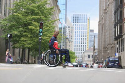 Man in wheelchair crossing a city street