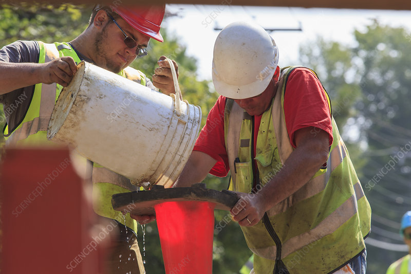 Construction workers pouring water