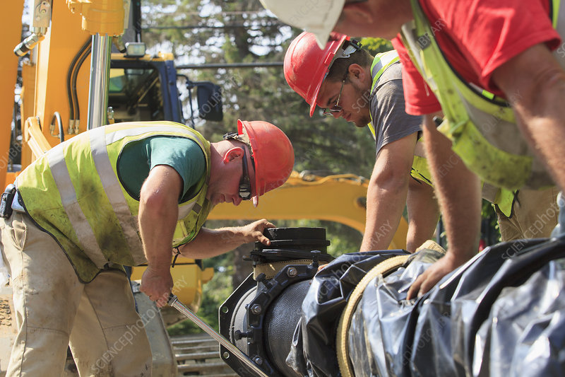 Construction workers using torque wrench