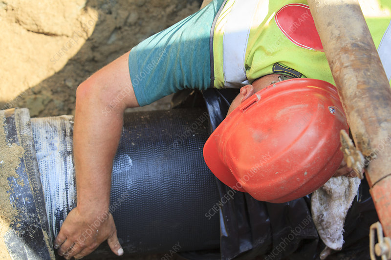 Construction worker placing water main