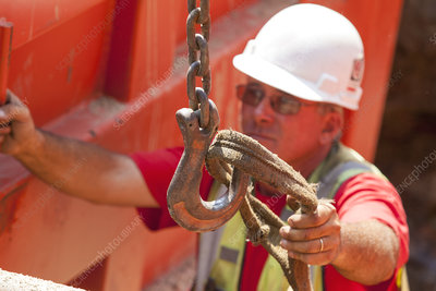 Construction worker placing lifting strap