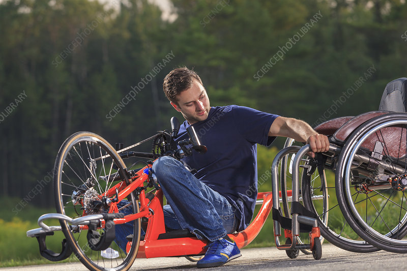 Man on hand cycle getting into wheelchair