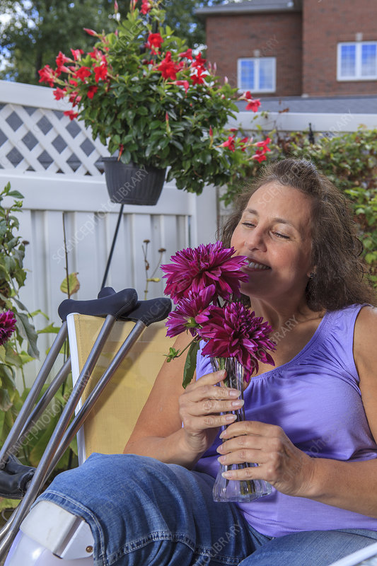Woman with disability smelling flowers