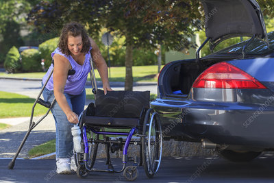 Woman putting her wheelchair in car