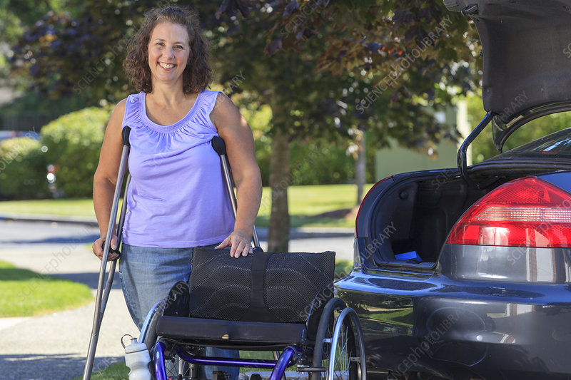 Woman near her wheelchair and car