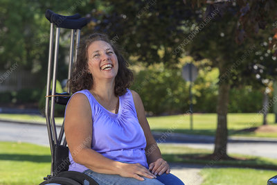 Woman sitting in wheelchair with crutches