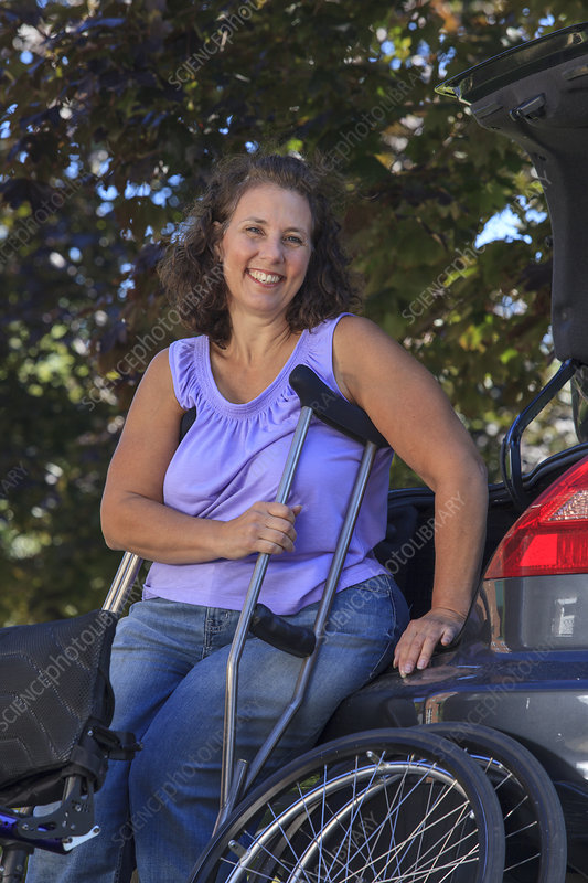 Woman using crutches and relaxing on car
