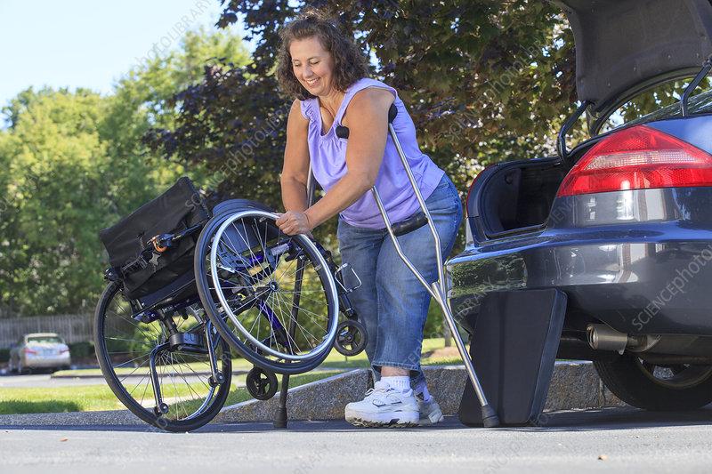 Woman using crutches to set wheelchair