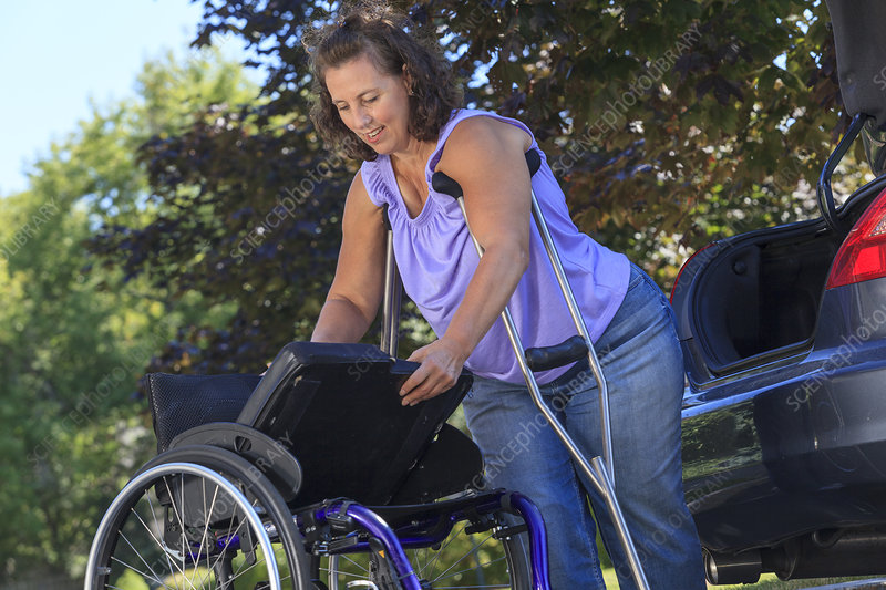 Woman using crutches to set wheelchair