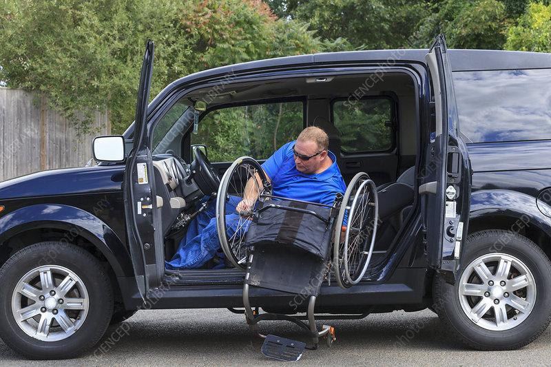 Man putting his wheelchair in his car