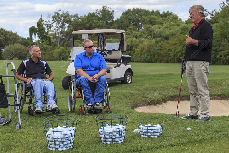 Two men in wheelchairs learning golf