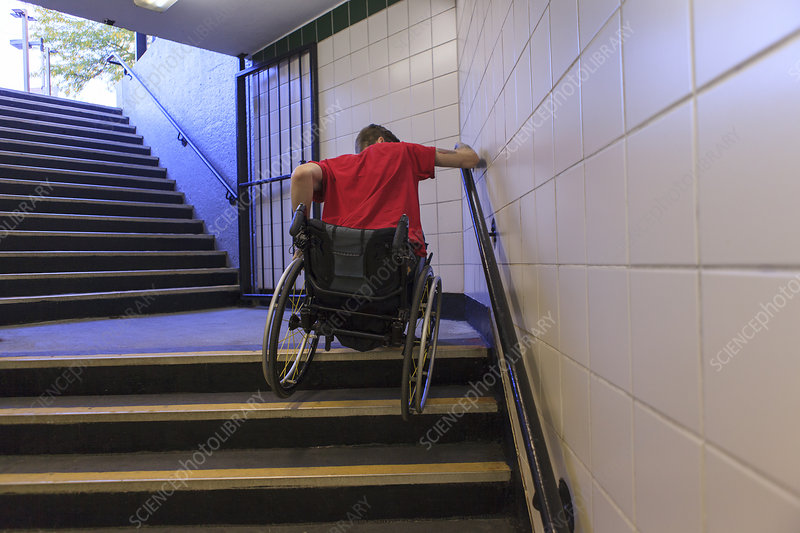 Man in wheelchair on subway stairs