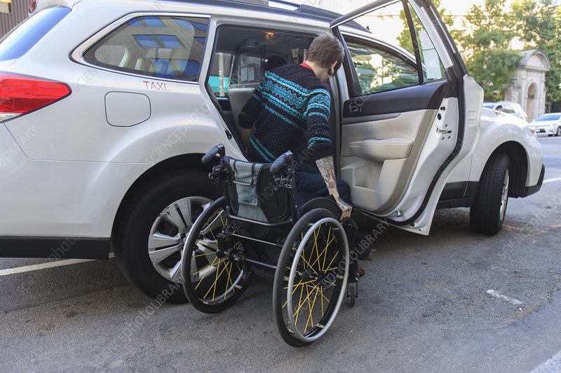 Man in wheelchair inside a taxi cab