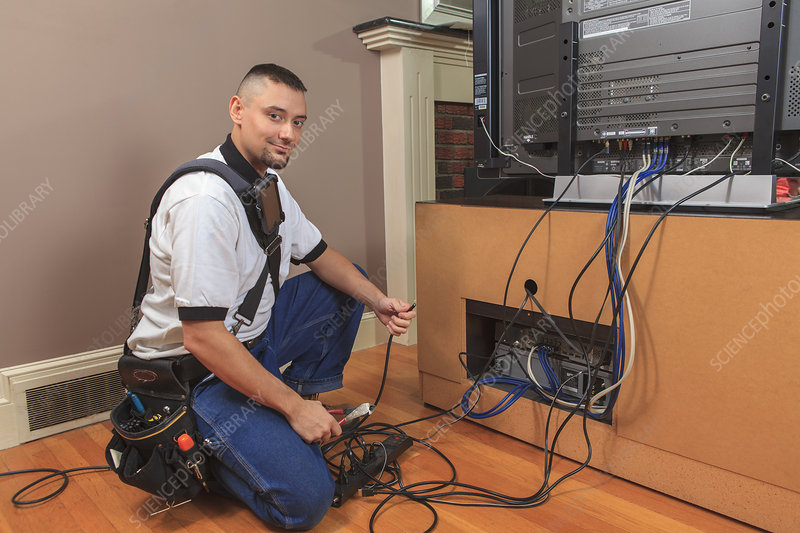 Cable installer working with TV in a home