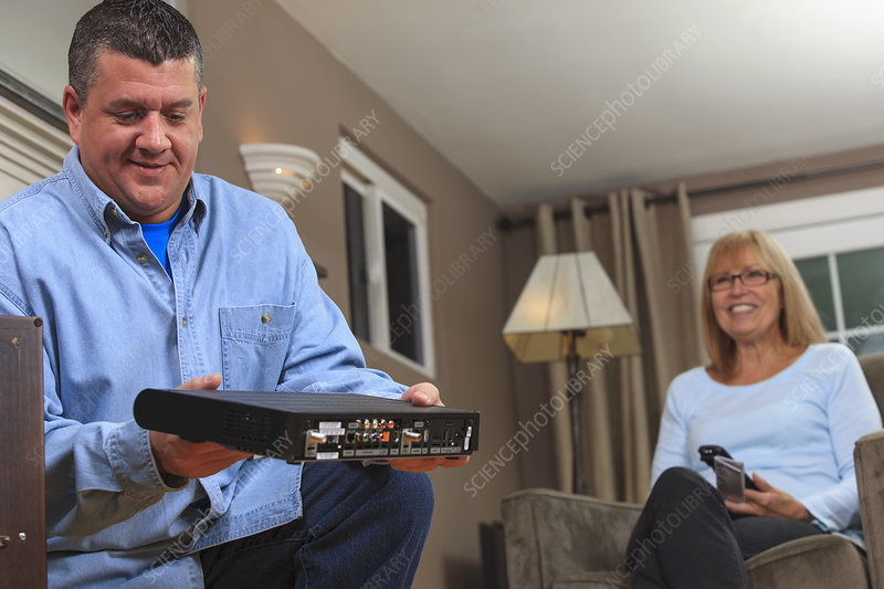 Service man installing a cable box